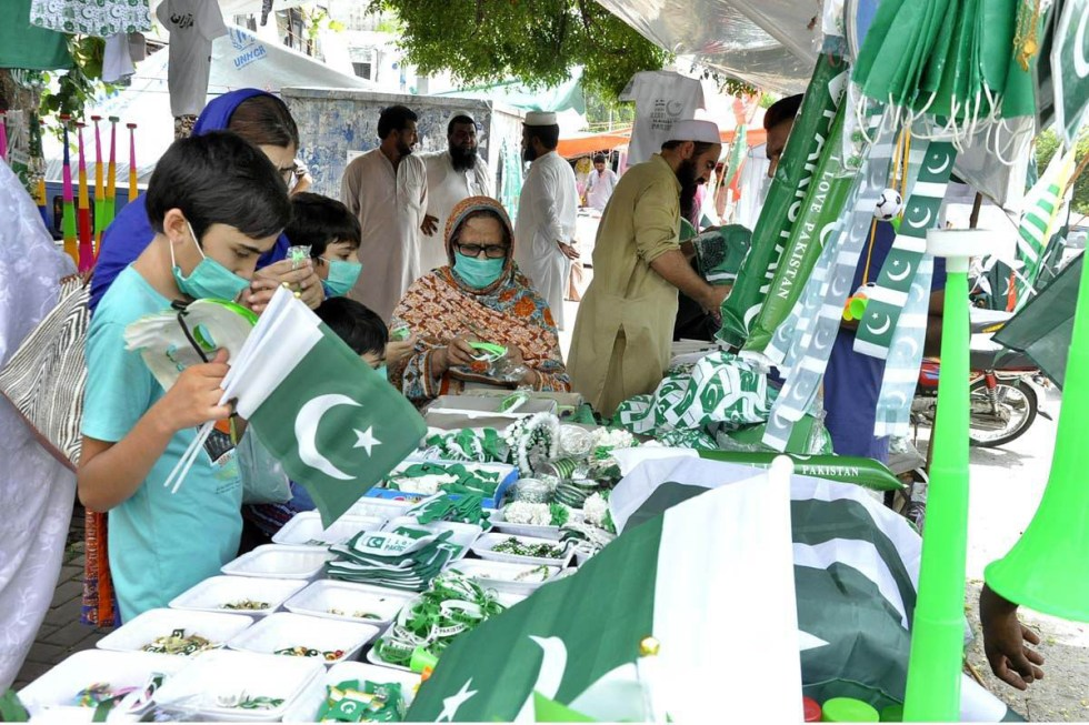APP03-13 ISLAMABAD: August 13 – People busy in purchasing national flags and other related stuff in connection with Independence Day for preparation to celebrate the Independence Day in befitting manners. APP photo by Saleem Rana