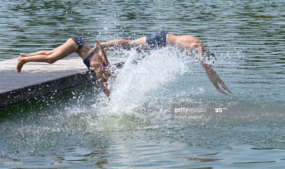 09 August 2020, Saxony, Radebeul: Bathers jump from a jetty into the water at the Mockritz natural pool. Photo: Robert Michael/dpa-Zentralbild/dpa (Photo by Robert Michael/picture alliance via Getty Images)