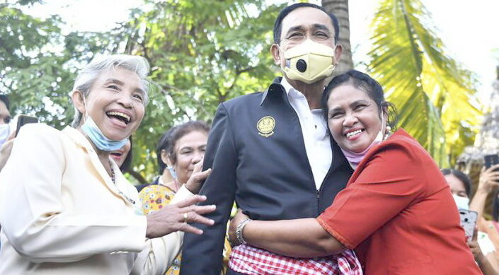 In this photo released by Government Spokesman Office, a well-wisher hugs Thailand's Prime Minister Prayuth Chan-ocha in Samut Songkhram province, Thailand, Wednesday, Dec. 2, 2020. Thailand's highest court Wednesday, has acquitted Prayuth of breaching ethics clauses in the country's constitution, allowing him to stay in his job. (Government Spokesman Office via AP)