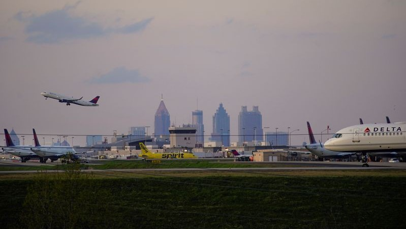 FILE PHOTO: The Atlanta skyline is seen behind Delta Air Lines passenger planes on a runway where they are parked due to flight reductions made to slow the spread of coronavirus disease (COVID-19), at Atlanta Hartsfield-Jackson International Airport in Atlanta, Georgia, U.S. March 21, 2020. Picture taken March 21, 2020. REUTERS/Elijah Nouvelage