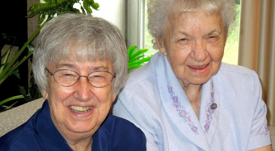 Sisters Jean Marie Hauck and Joan Wagner seated together and smiling