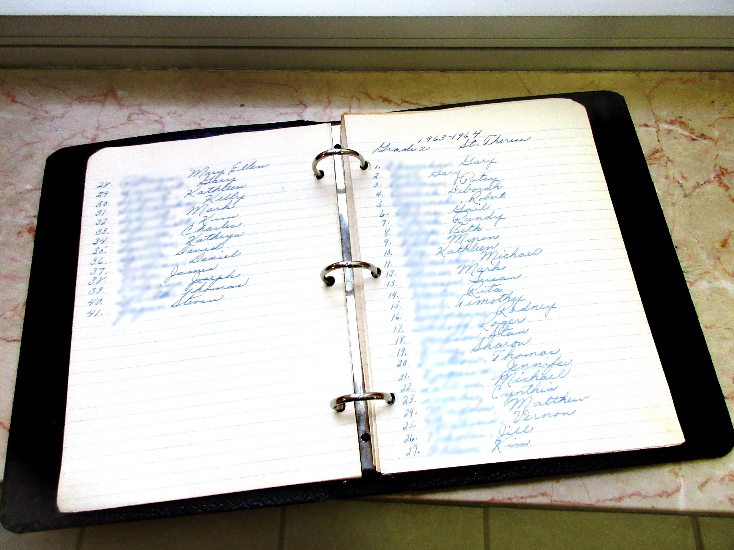 Pages from Sister Mary Jo's notebook in which she kept the names of each student throughout the years so she could continue to pray for them. Shown are from her 1963-1964 Second grade classroom.