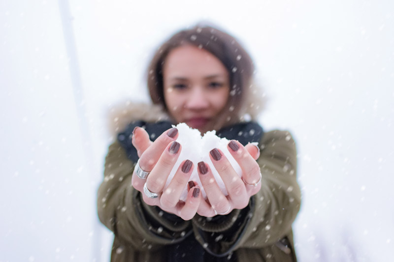 Woman holding snowball in hands