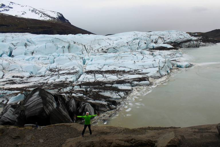 Gwen standing with arms spread wide in front of a glacier