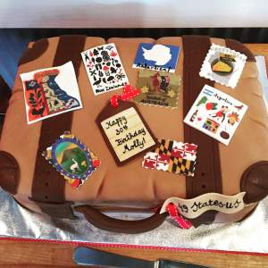 Cake decorated like an old brown suitcase with stamps from around the world