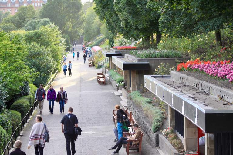 Path lined with flowers, trees, and benches in Princes Street Gardens