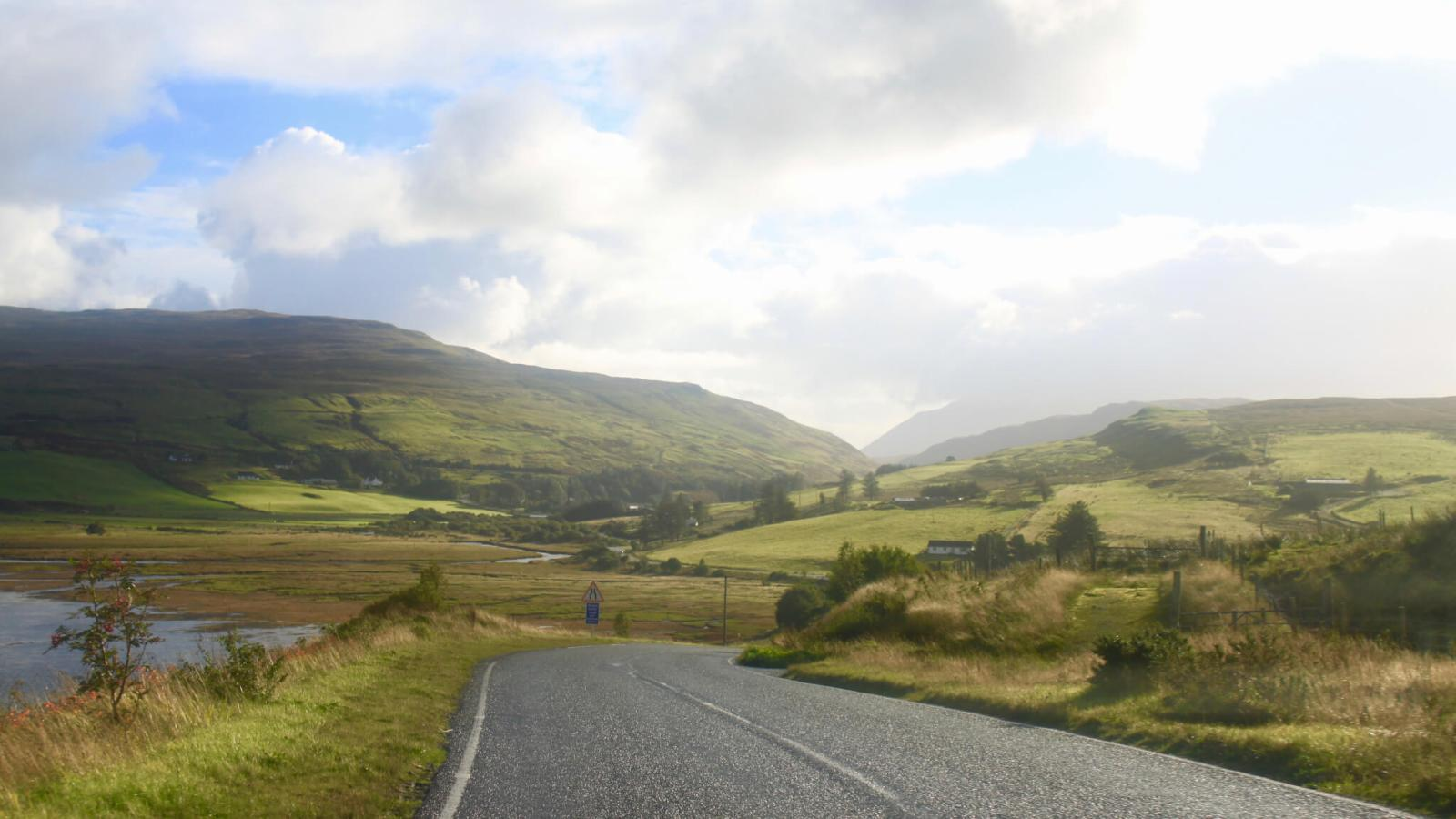 Road winding through the green and golden hills on an Isle of Skye driving itinerary.
