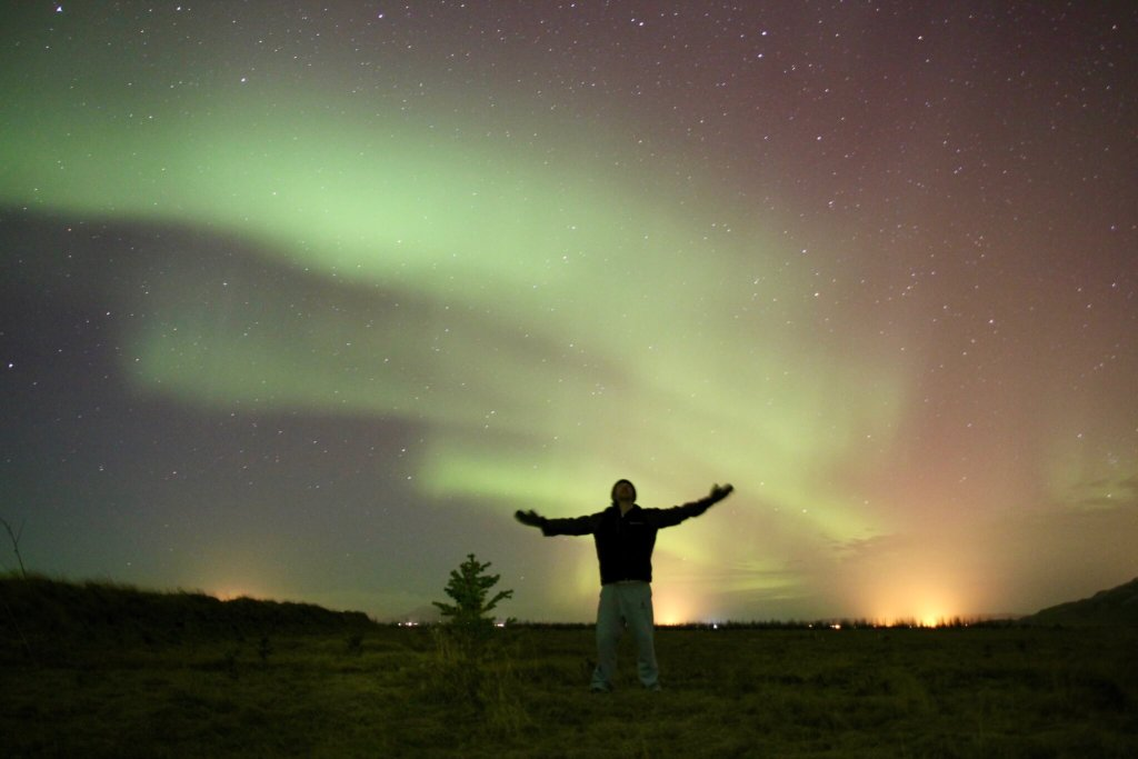 Max in silhouette with arms spread wide under the northern lights