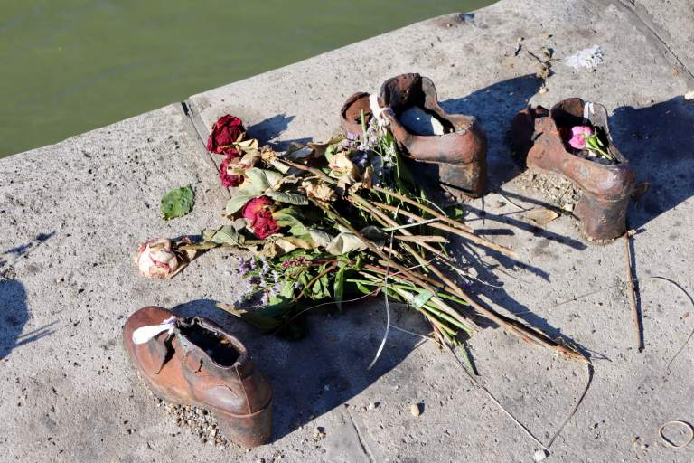 Flowers and candles placed with iron shoes in the Shoes on the Danube Bank memorial
