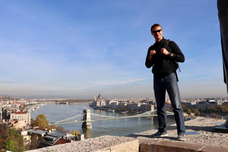 M in front of a panoramic vista of the Danube, with the Chain Bridge and Parliament Building in the distance