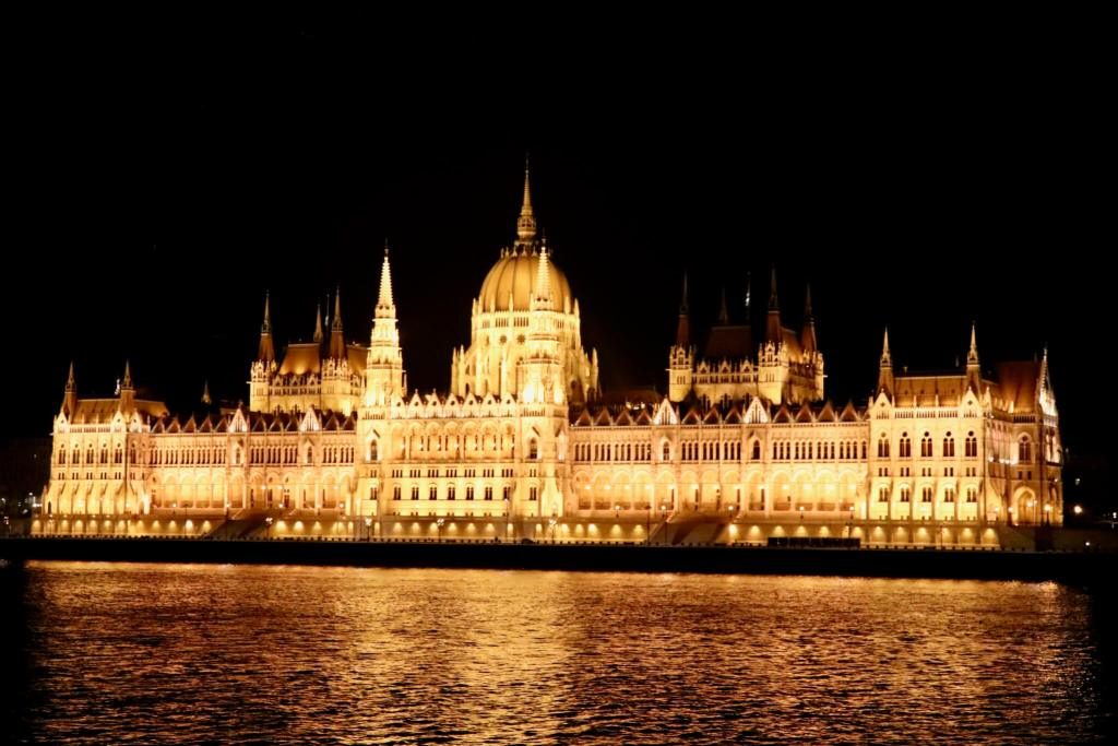 Parliament Building glowing golden, lit up at night in Budapest