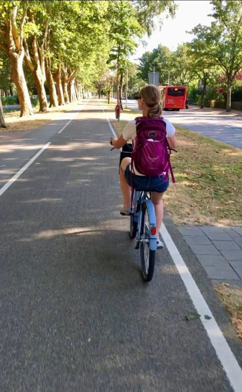 Gwen biking on bike path - a great way to stay healthy while traveling!