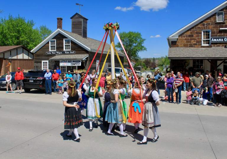 Women dancing around a maypole in traditional dress