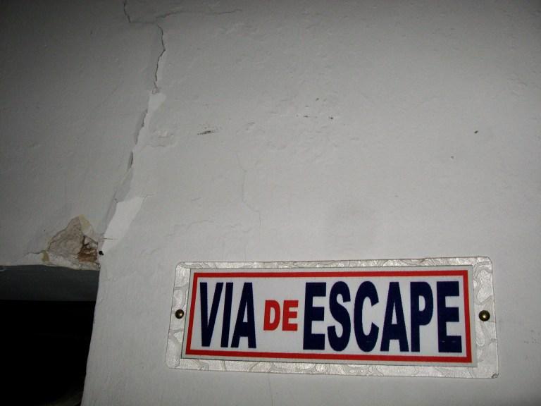 "Cracked wall next to ""Via de Escape"" (""Escape Route"") sign"