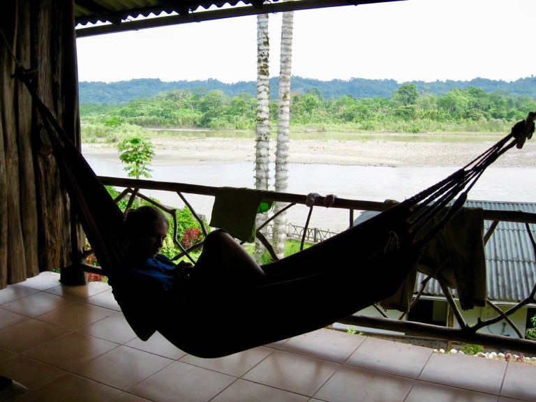 Gwen silhouetted in a hammock with the river and jungle behind