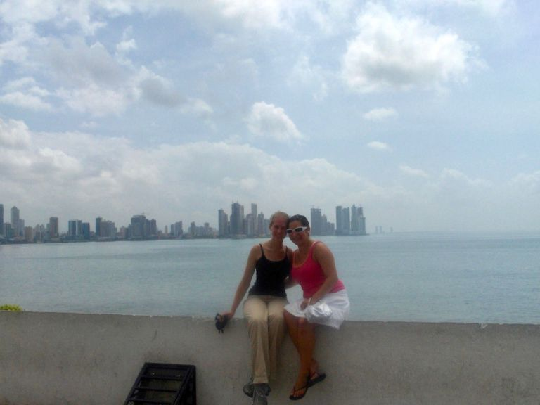 Gwen and friend Cristina sitting on a sea wall in front of Panama City skyline