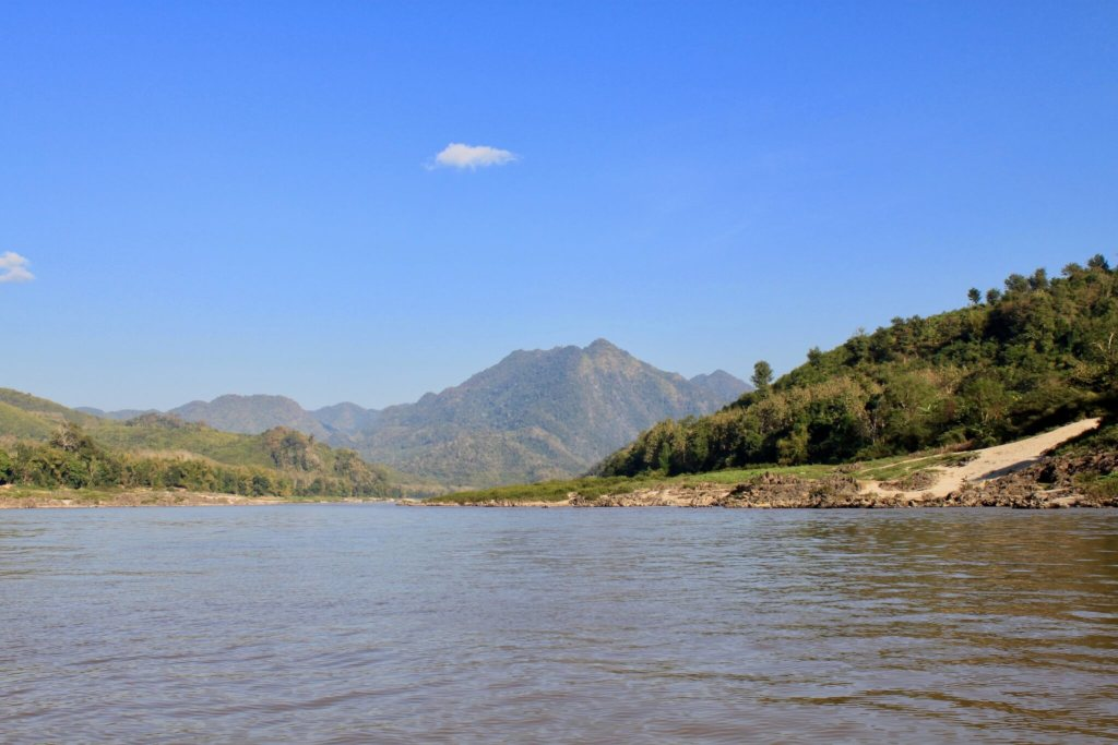 Green mountains, brown river, and blue sky