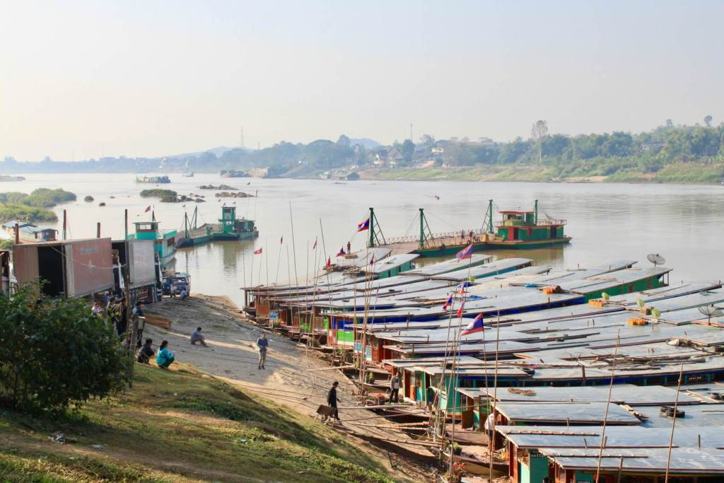 Numerous colorful longboats lined up side-by-side along the shoreline of the Mekong River