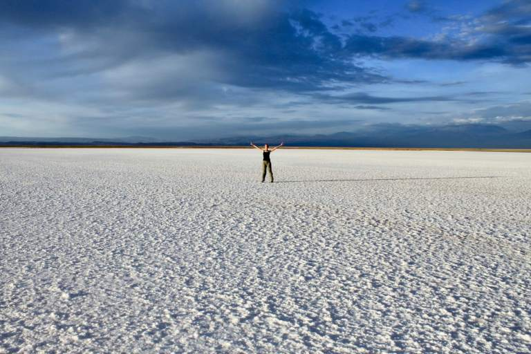 Gwen standing with arms spread wide in the middle of the salt flat