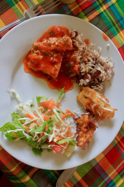 Creole food on a white plate on top of a colorful plaid tablecloth