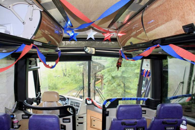View from interior of tour bus out front windshield with streamers and stars and other patriotic decorations