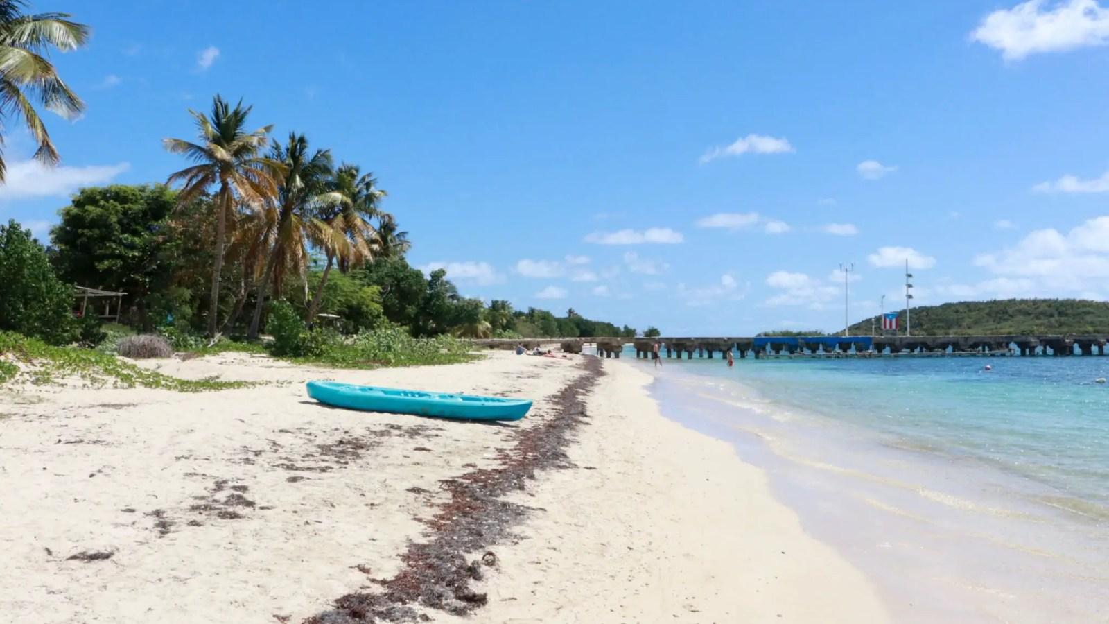 Blue kayak on Esperanza Beach, Vieques, with pier in background