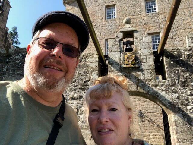 Vacation planning client couple in front of Scottish castle