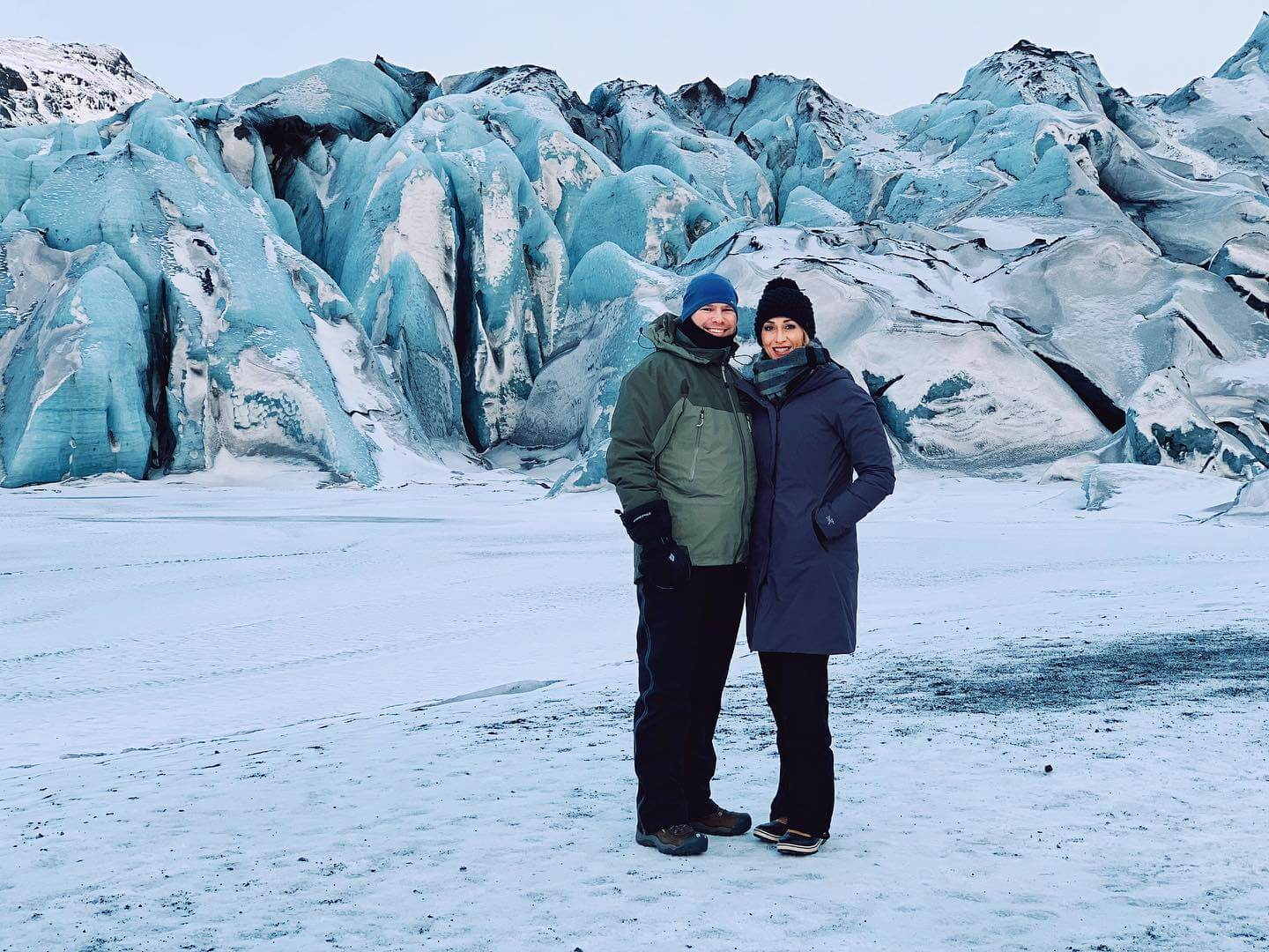 Vacation planning client couple standing in front of an Icelandic glacier