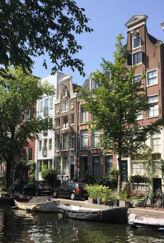 Shaded row houses and boats along Amsterdam canal