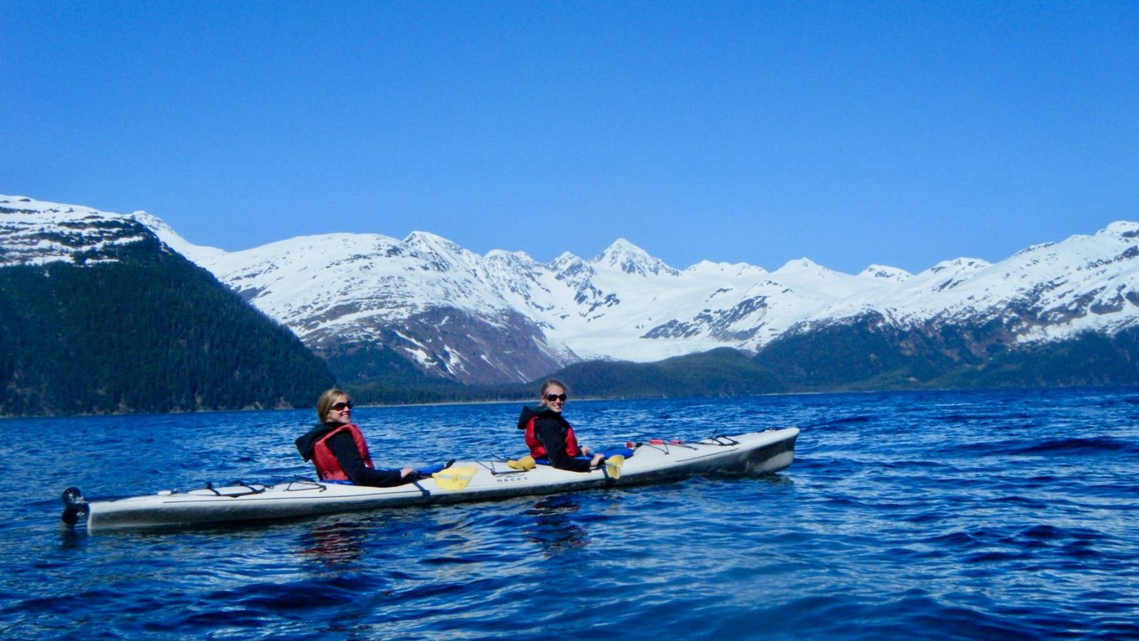 Gwen and a friend kayaking in front of snow-capped mountains