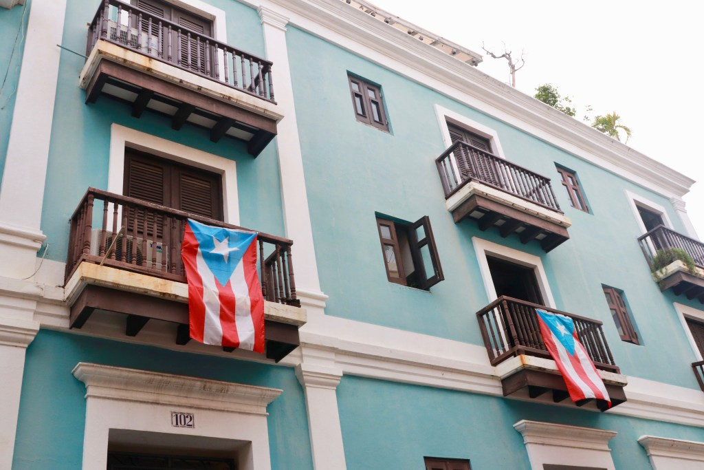 Puerto Rican flags hanging from dark wooden balconies on a teal building in Old San Juan