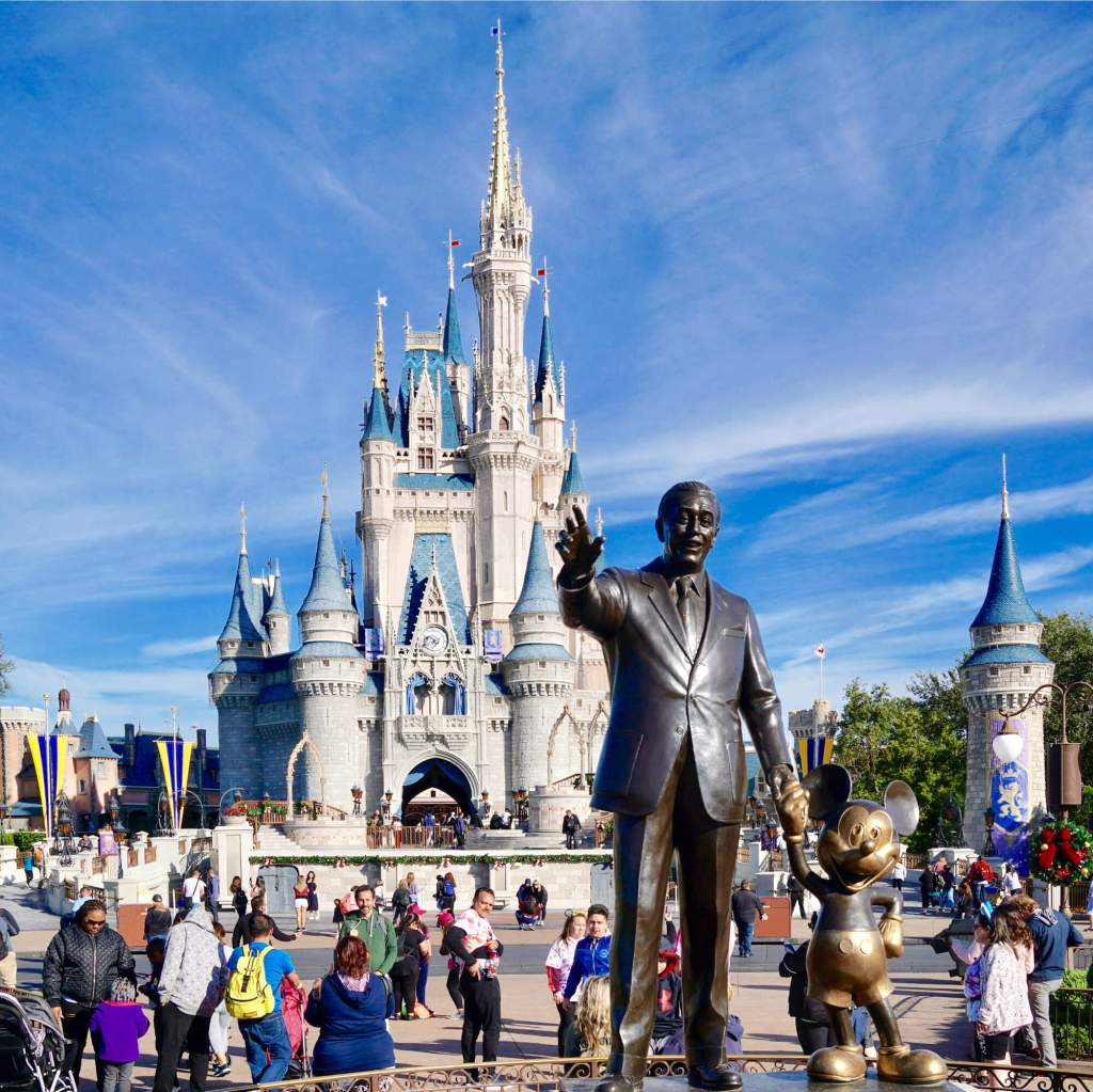 Statue of Walt Disney and Mickey Mouse holding hands in front of Cinderella's Castle