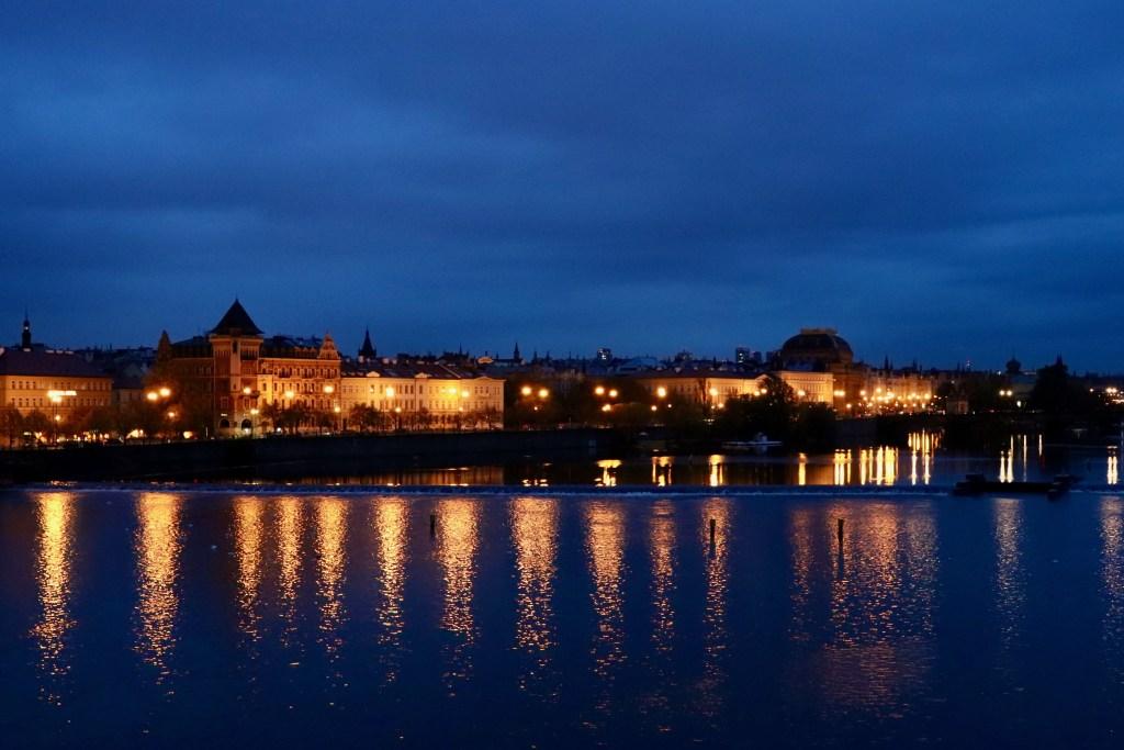 Prague riverfront lit up in the pre-dawn light
