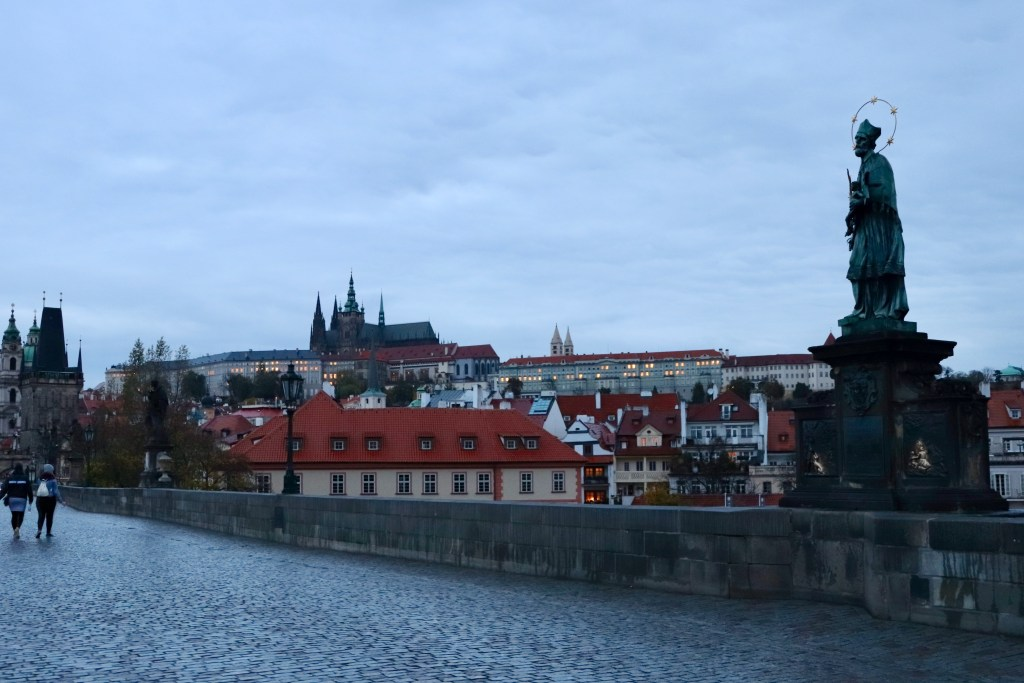 Statues and castle coming into view at dawn on the Charles Bridge