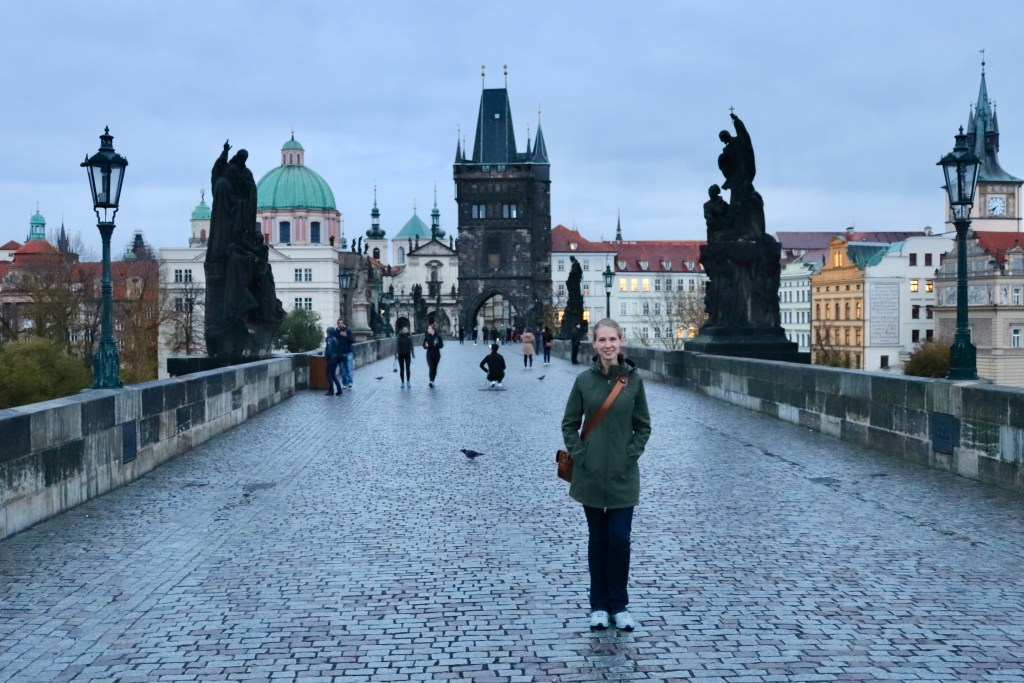 Gwen on the nearly-empty Charles Bridge as dawn transitions to morning.