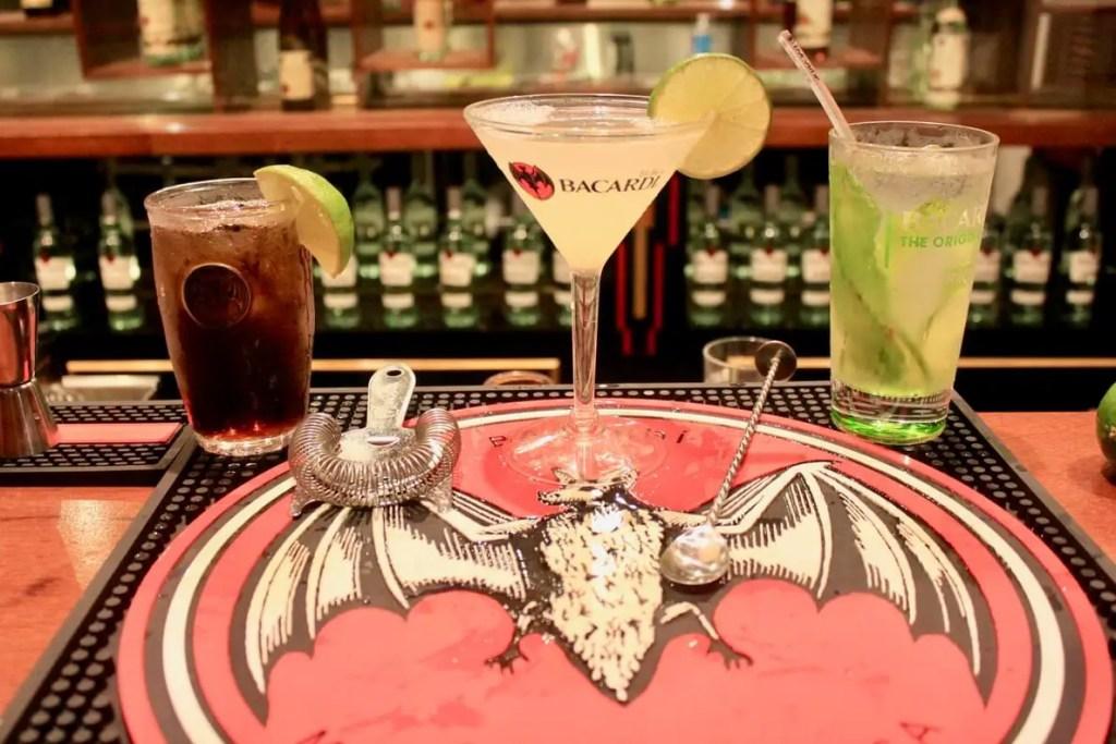 Mixed cocktails on a mat bearing the Bacardi bat logo