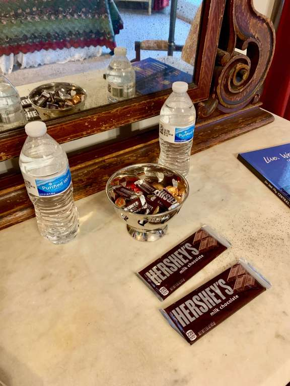 Two water bottles, two Hershey bars, and a bowl of miniature Hershey candies