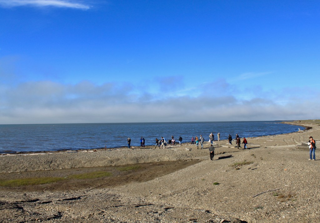 People gathered on the shoreline of the Arctic Ocean