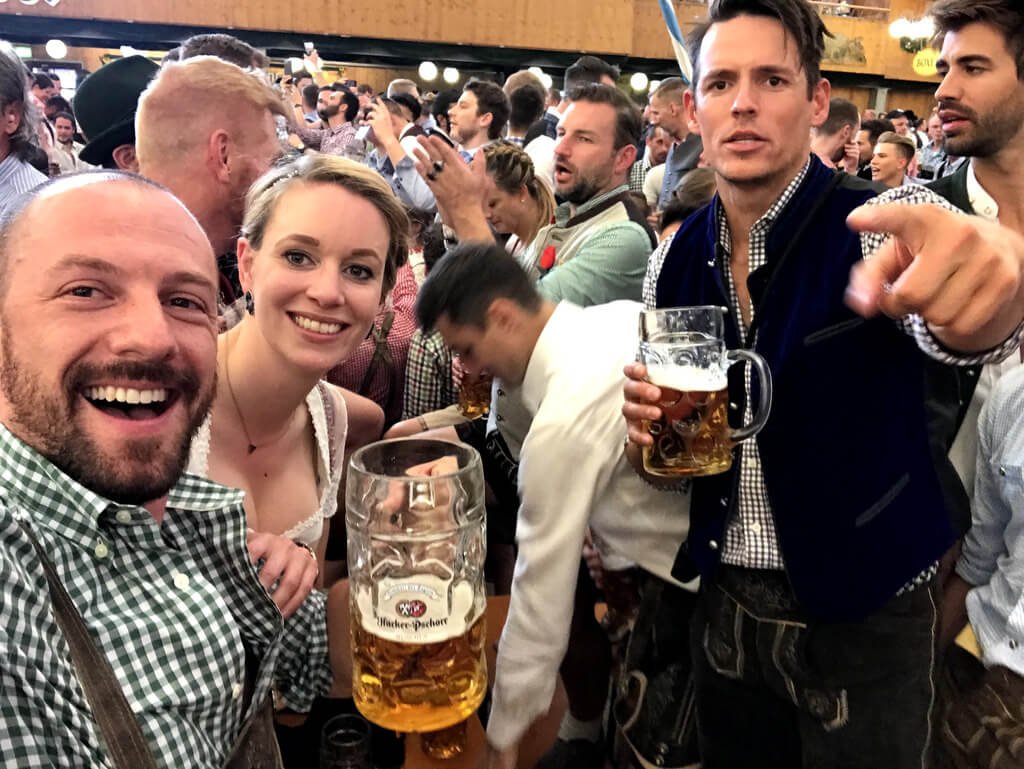 Max holding a beer with friends at Oktoberfest in Germany