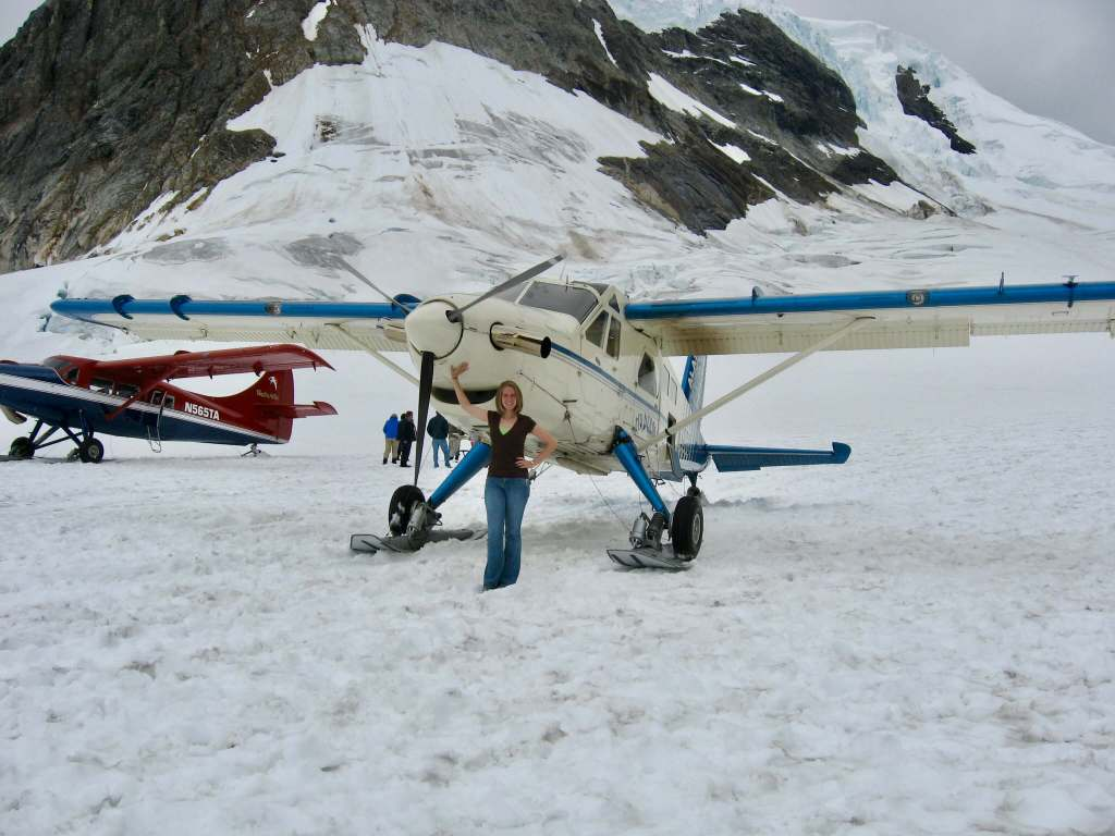 Gwen next to a prop plane on a glacier in Denali National Park and Preserve