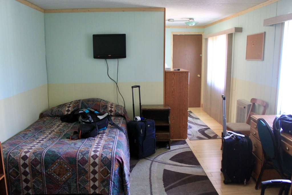 Bare-bones room at the Arctic Caribou inn with bed and dresser and suitcases