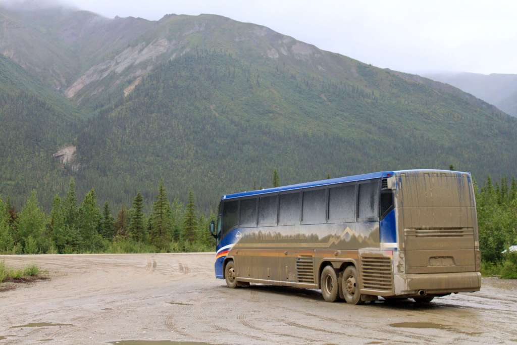 Motorcoach caked with mud from driving Alaska's Dalton Highway