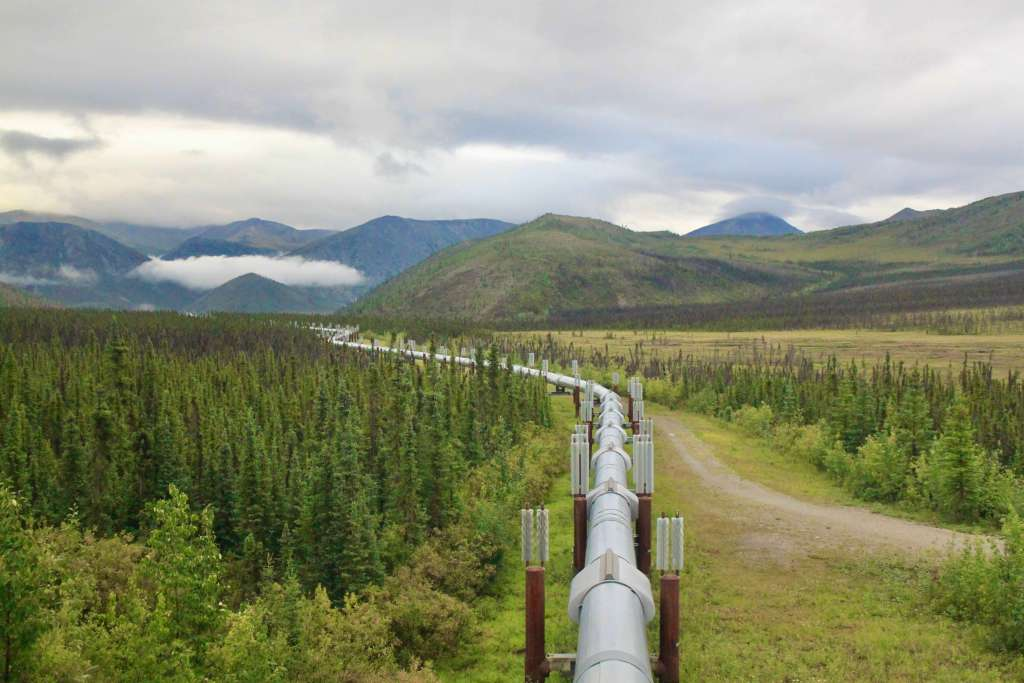 The Alaska Pipeline stretching off into the distance through evergreen forests and mountains