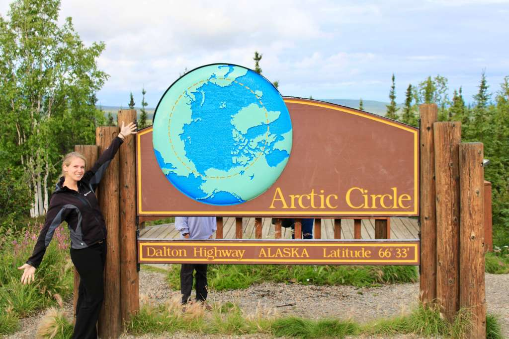 Gwen in front of a sign marking the Arctic Circle