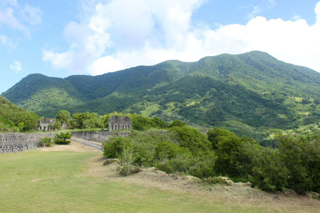 The green volcanic mountains of St. Kitts with fort ruins in the foreground.