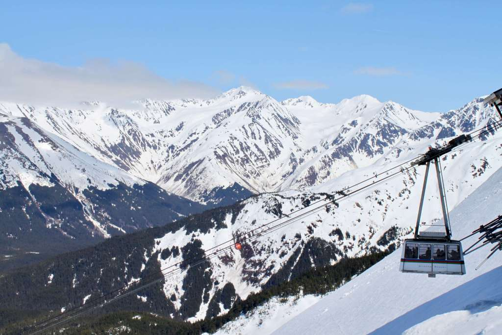 Alyeska's aerial tram suspended in front of snow-capped mountains.