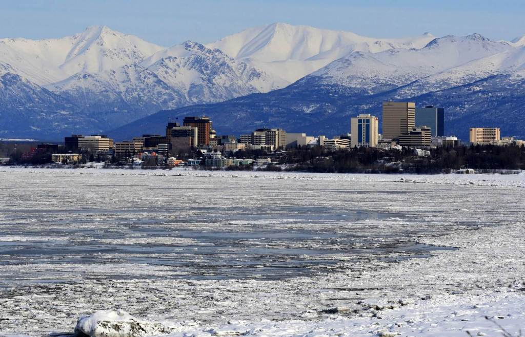 Anchorage skyline with snow-capped mountains beyond. Anchorage is a great first stop on your Alaska itinerary.