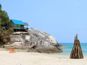 Bungalow perched on a huge boulder and bonfire pyre on the sand