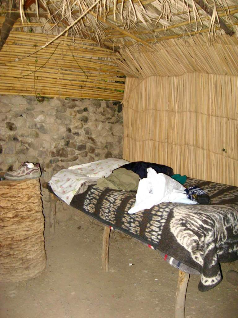 Inside the bamboo hut: a rustic bed with blankets