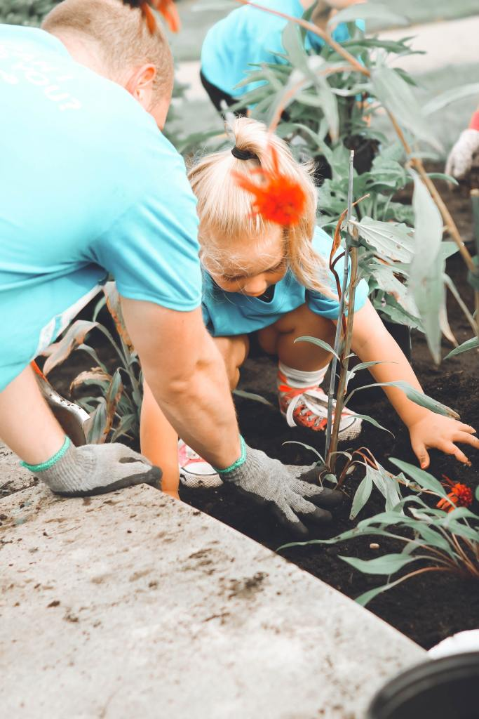 A girl and and a man planting. giving back to the earth